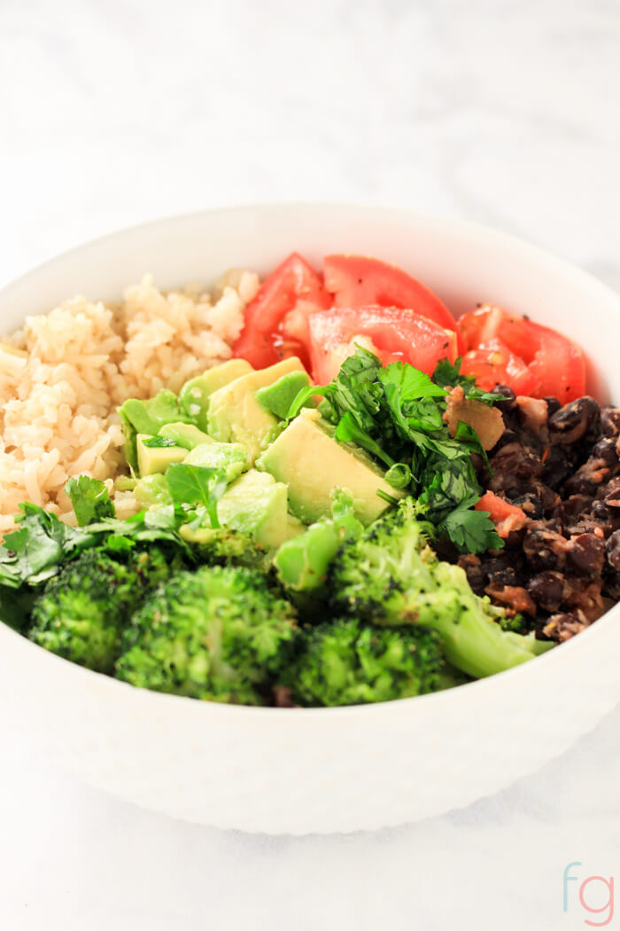 white bowl filled with fresh vegetables and rice to make this vegan buddha bowl.