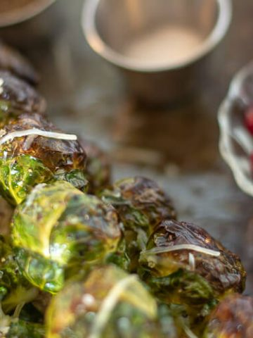 Roasted Brussel Sprouts on a Sheet Pan with a Small Bowl of Cranberries in the Background