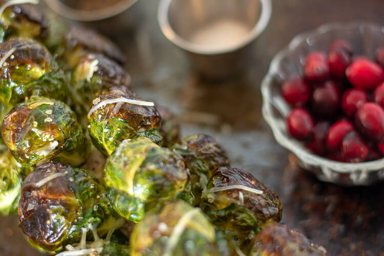 Roasted Brussel Sprouts on a Sheet Pan with a Small Bowl of Cranberries in the Background.