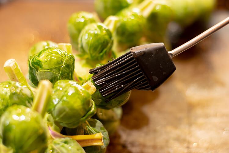 Brushing Olive Oil on the Brussel Sprout Stalk Resting on the Sheet Pan.