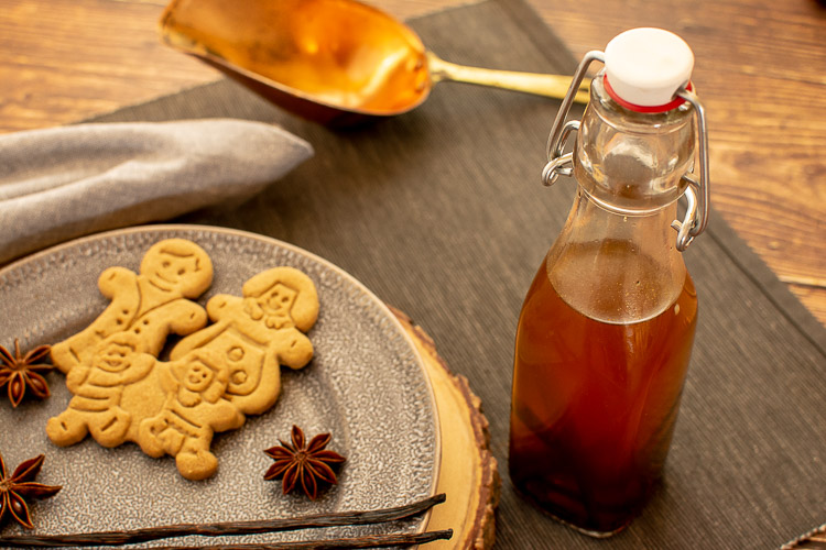 vanilla beans in the vodka in a decorative bottle with a plate of cookies and spices.