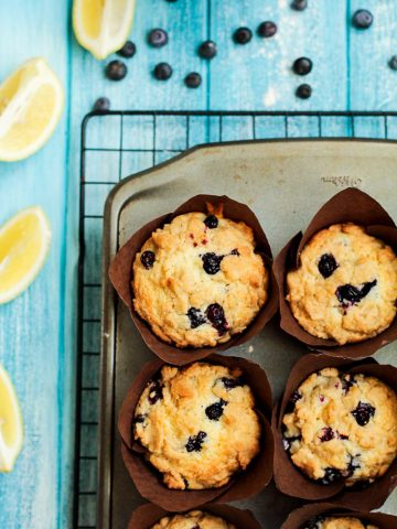 Six Muffins on a Cooling Rack with Cut Lemons and Loose Blueberries on a Blue Table