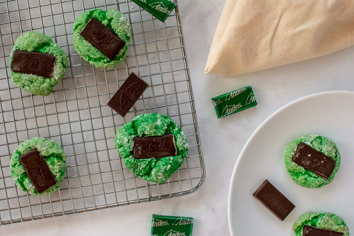 Top down view of green mint cookies, wrapped and unwrapped Andes mints and a plate ready to serve