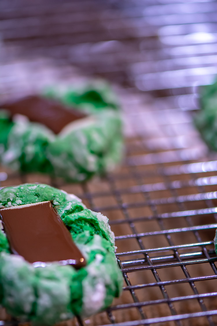 green cookies on a cooling rack with the andes mint chocolate melting