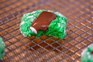 A bite out of the green cookie and chocolate mint. It is resting on a cooling rack.