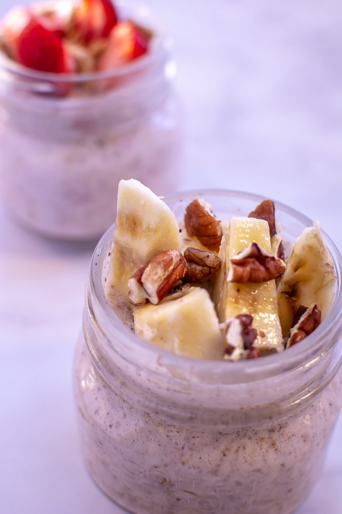 Bananas and Pecans top this overnight oat in a small glass jar