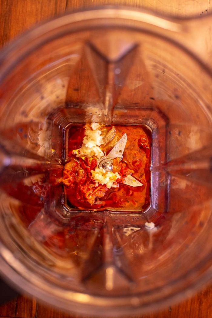 Top down view of the Vitamix high speed blender with tahini, garlic and roast red peppers to make the sauce