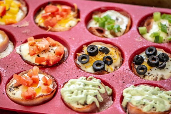 Closeup of Muffin Tin with each cup topped with different vegetables and sauces