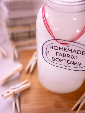 Large Mason Jar filled with homemade fabric softener. Clothes Pins and laundry towels are in the background. A cute label that read homemade fabric softener is hanging on a red ribbon