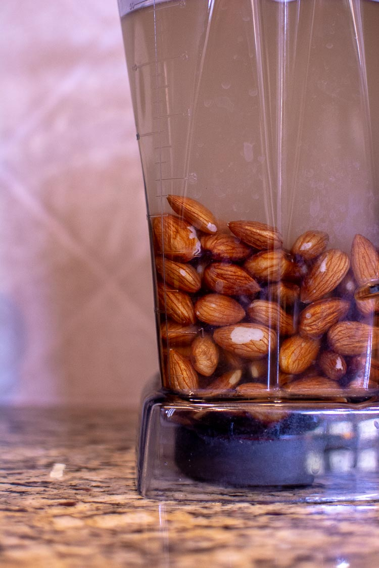 All of the ingredients are added to the Vitamix. The Almonds are in the container with the water