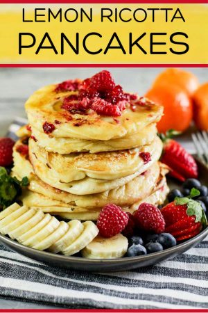 Delicious Raspberry Lemon Ricotta Pancakes Ready for a Special Breakfast. Surrounded by Fresh Fruit, this is a Fantastic Morning Treat #Pancakes #LemonPancakes #RicottaPancakes #Breakfast