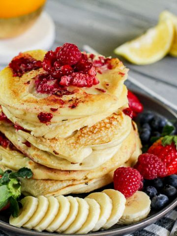 Plated Raspberry Lemon Ricotta Pancakes surrounded by fresh fruits