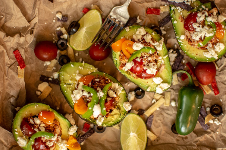 Four stuffed avocados on butcher paper garnished with peppers, olives, feta, and limes.