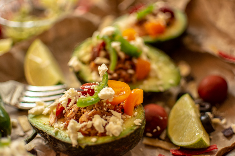 Closeup of a chicken stuffed avocado and topped with peppers, feta and corn chips.