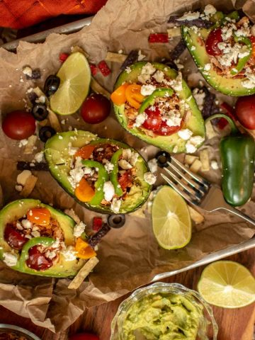 Cut avocados in half and fill them with a small portion of meat and veggies. There are four on a butcher paper covered sheet pan.