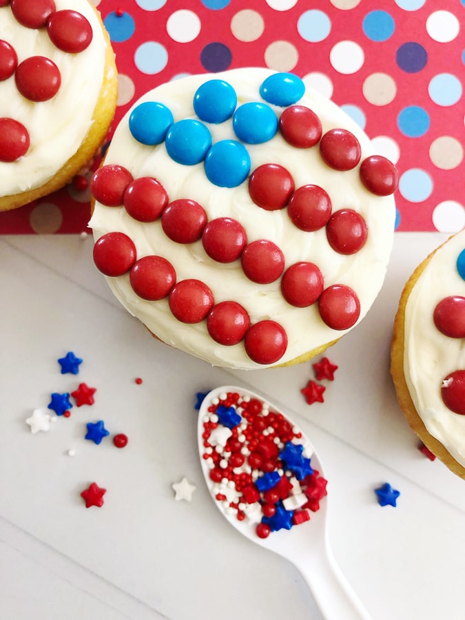 top down view of cupcake with white icing and red and blue M&Ms that form and american flag