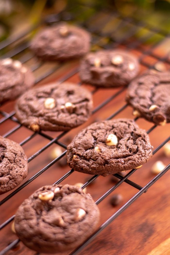 Several cookies on a cooling rack with chocolate chips sprinkled throughout