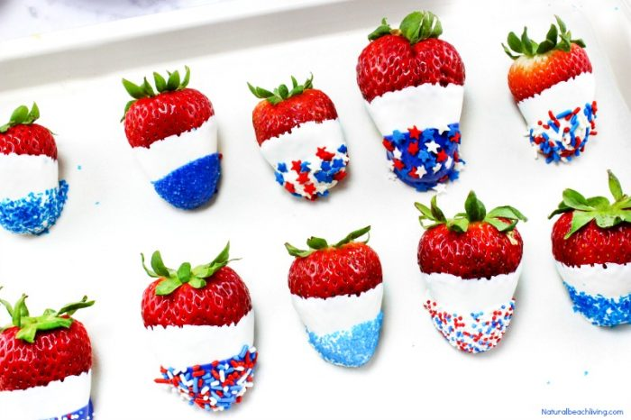 strawberries dipped in white chocolate and rolled in different types of blue sprinkles to make a 4th of july treat
