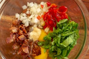 Glass bowl with garlic and onion powder, bacon, onion, red pepper and spinach