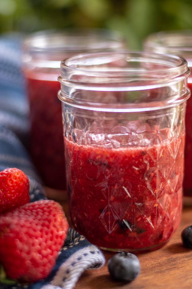 Mason jar with mixed berry jam poured inside