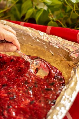 Spreading the jam across the oatmeal crust to form the center of the jam bars