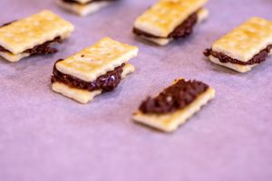 several keebler mini crackers with nutella sandwiched on wax paper