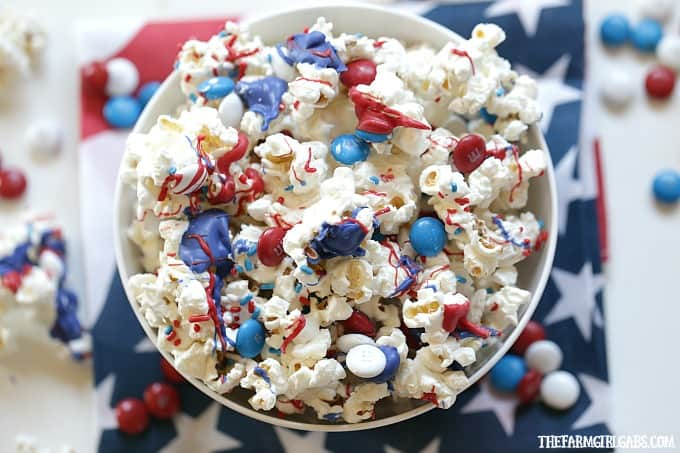 bowl of popcorn with dyed melted white chocolate and M&Ms for a patriotic snack