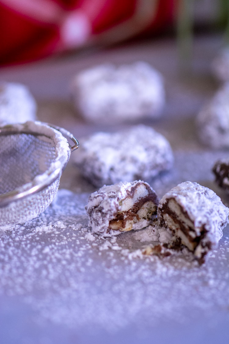 Powdered Sugar and a sifter covering the bites