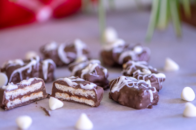 Whit chocolate drizzled on top of the crackers with white chocolate chips in the foreground