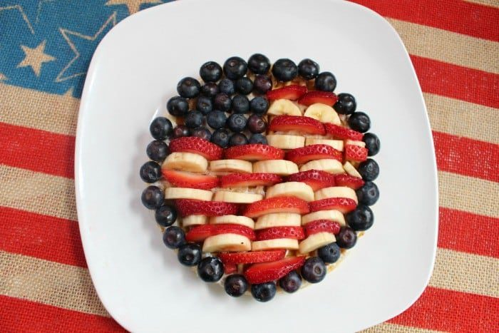 Waffle covered in bananas, strawberries and blueberries in the shape of old glory flag