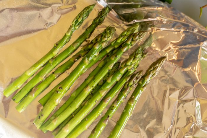 Several Spears of Asparagus on a piece of aluminum foil to start the recipe