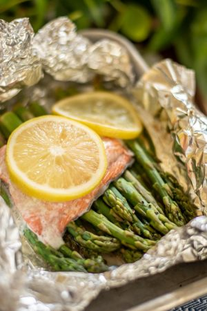 Bright Yellow Lemons on the salmon and asparagus in a foil packet