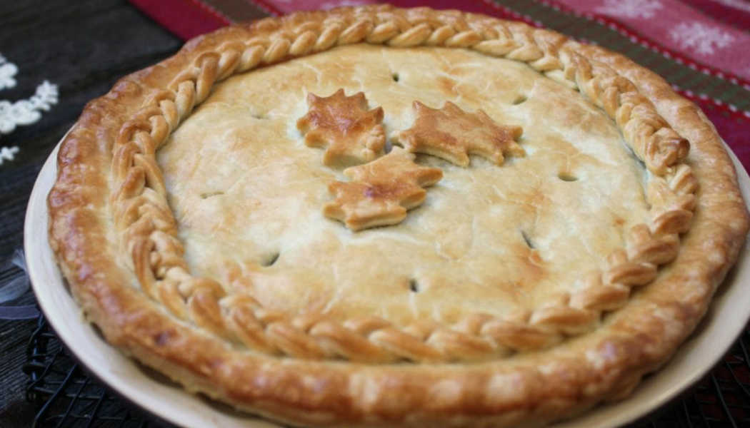 Pie tin with a tourtière and leaf shaped pastry topping