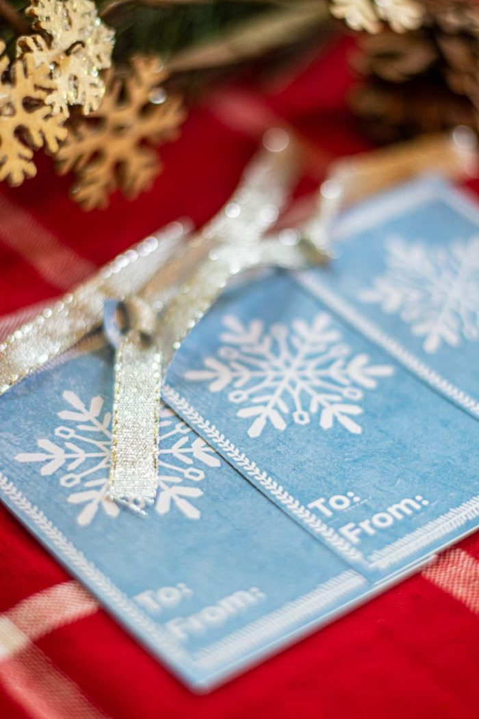 Three blue free gift tags with silver ribbon and a white snowflake.