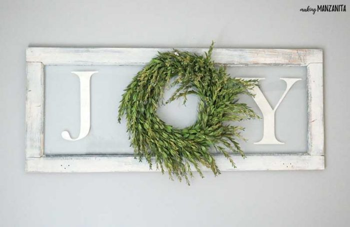recycled window with a wreath and spelling the word Joy