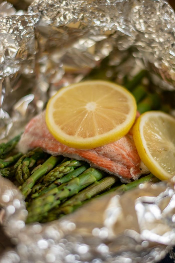 Fresh out of the over, the foil wrap is opened revealing a fully cooked salmon fillet and bright green cooked asparagus