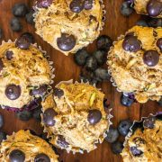 Top down view of healthy blueberry zucchini muffins on a wooden cutting board