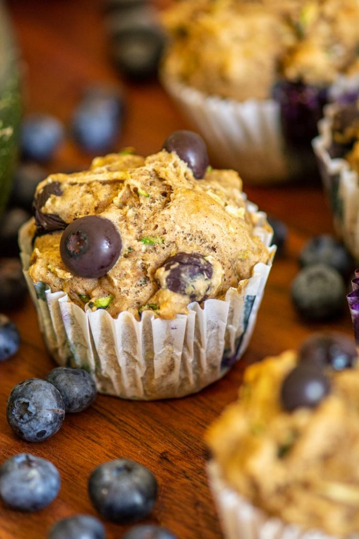 Single Baked Blueberry Zucchini muffin on a wooden cutting board