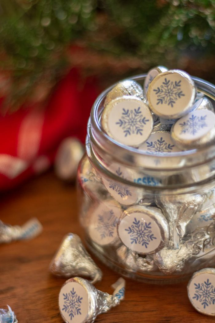Small jar filled with silver hershey kisses with avery label stickers on the bottom with snowflakes.