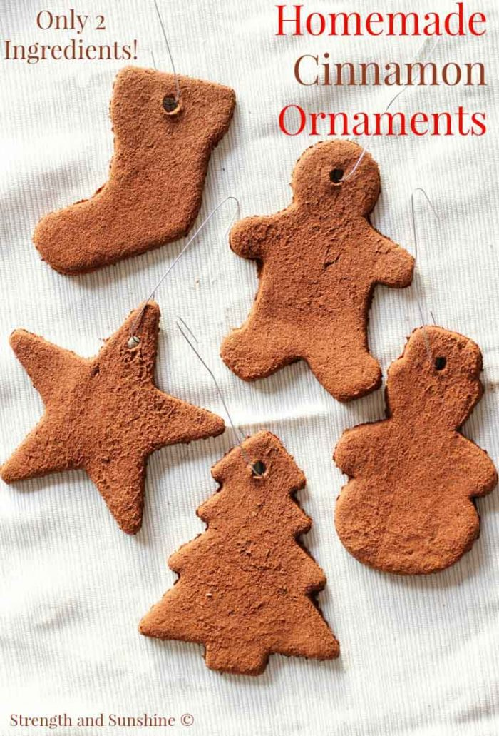 Several simple cinnamon ornaments with christmas tree hooks on a linen background