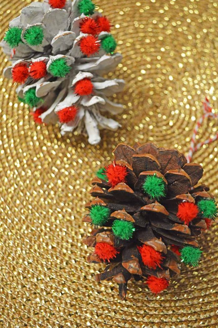 red and green pom pom ornaments on pinecones for a home made frugal decoration idea