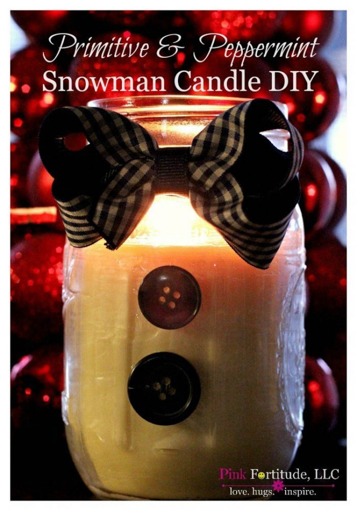 Mason Jar decorated like a snowman with wax and a burning candle