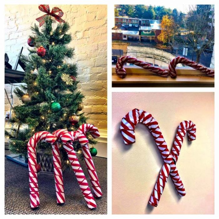 Wrapped Cardboard candy canes leading against a christmas tree