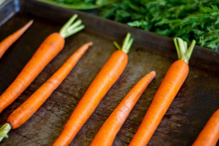 Whole carrots lined on a sheet pan