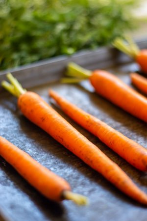 Whole carrots on the sheet pan before going into the oven