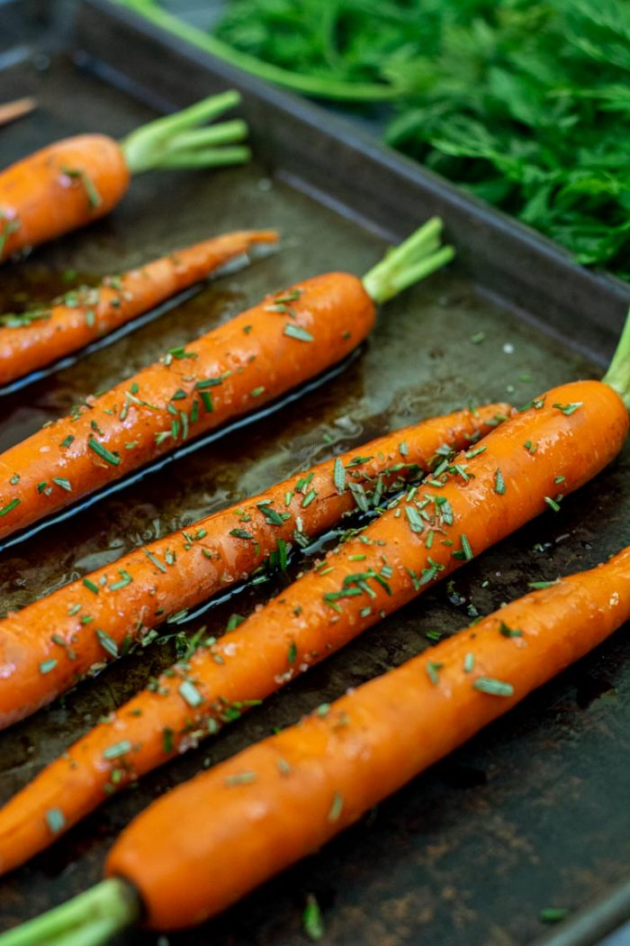 Sprinkle herbs on the carrots on the sheet pan before they go in the oven. Use unpeeled carrots
