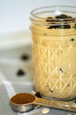 Front on shot of mocha overnight oats in a mason jar with a spoon of espresso powder and oats sprinkled on the table