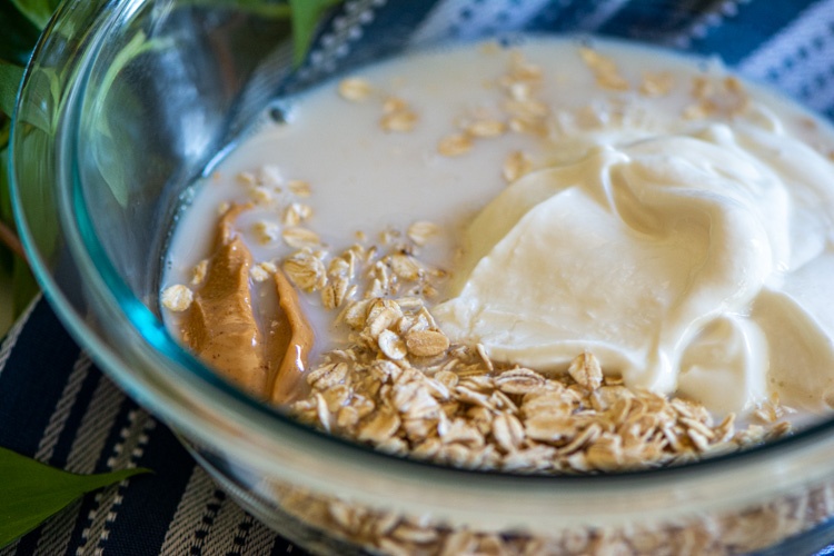 Glass bowl with oats, peanut butter, yogurt, and almond milk