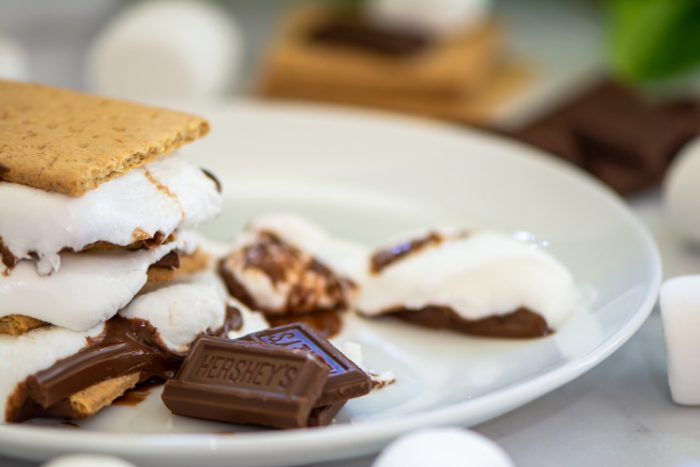After heating, the chocolate and marshmallow will melt and form that unmistakable s'more! On a white plate melted and still warm.