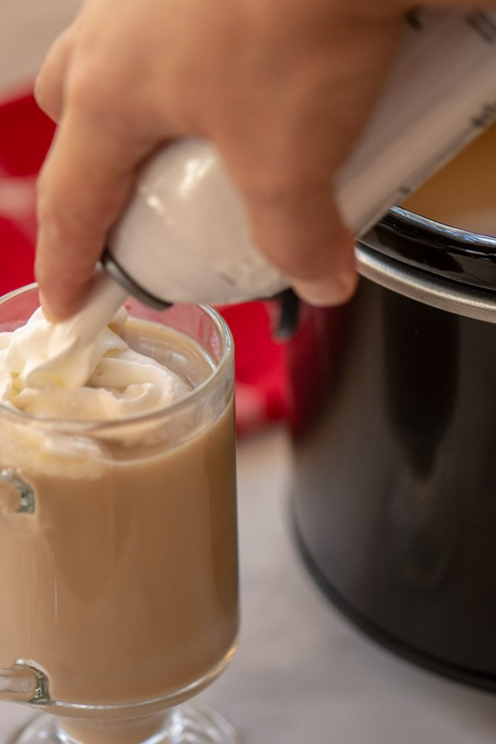Adding Whipped Cream to the top of the christmas coffee
